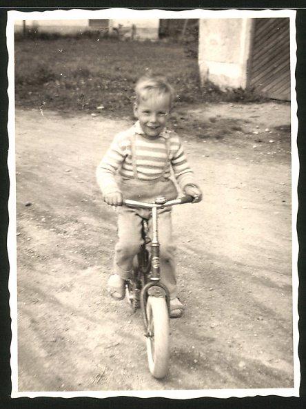 Fotografie fröhliches Kind fährt Fahrrad