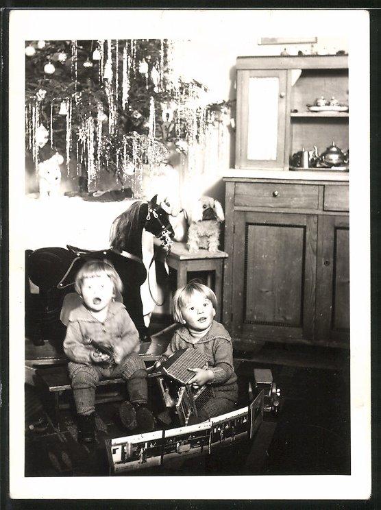 Fotografie Weihnachten, Kinder spielen mit Blechauto, Spielzeug-Pferd steht am Weihnachtsbaum