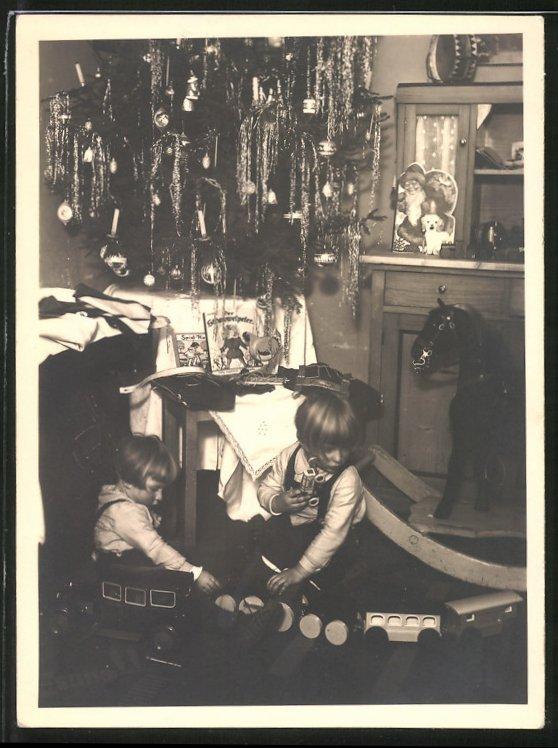 Fotografie Weihnachten, Kinder spielen mit Spielzeug-Eisenbahn und Blechauto unter dem Weihnachtsbaum