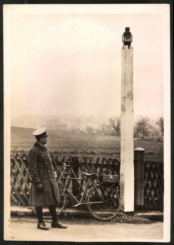 Fotografie Schutzmann mit Fahrrad neben Strassenlaterne stehend