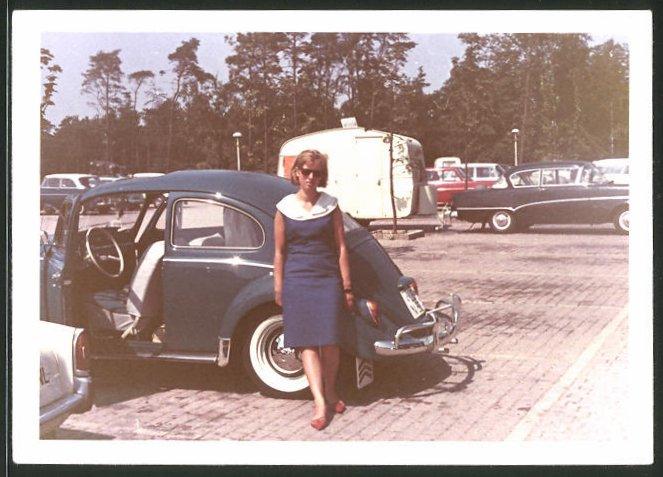 Fotografie Auto VW Käfer, hübsche Frau neben Volkswagen PKW auf einem Parkplatz
