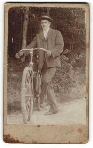 Fotografie junger Mann mit Fahrrad im Grünen