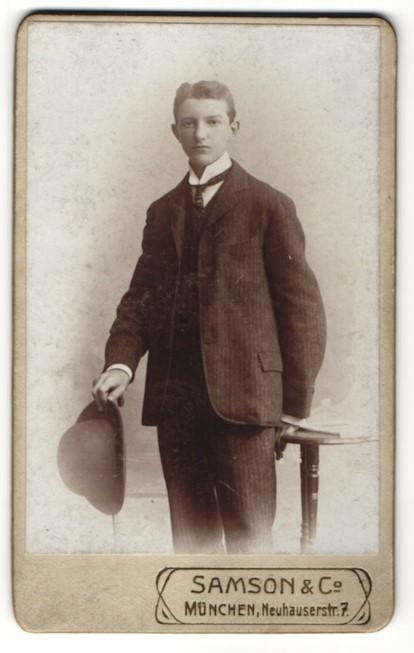Fotografie Atelier Samson & Co., München, Portrait junger Mann im Anzug mit Hut
