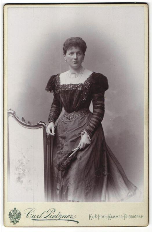 Fotografie Carl Pietzner, Wien, Dame mit Federfächer trägt elegantes Abendkleid