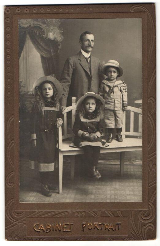 Fotografie Fotograf & Ort unbekannt, Vater mit Sohn und Töchtern im Foto-Atelier