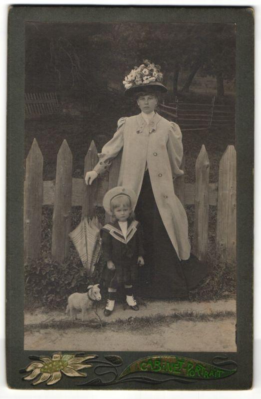Fotografie Fotograf & Ort unbekannt, Dame mit modischem Hut nebst Tochter in Marine-Uniform, Spielzeug-Schaf