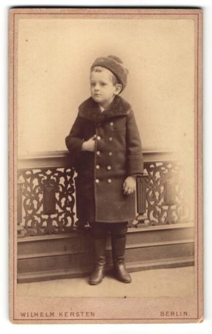 Fotografie Wilhelm Kersten, Berlin-SW, Portrait Knabe in Wintermantel mit Pelzmütze