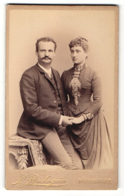 Fotografie Rud. Bradengeier, Düsseldorf, Ehepaar zünftig gekleidet hält Händchen