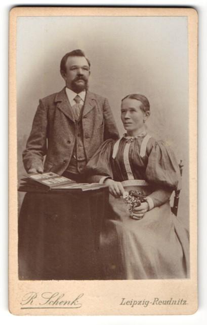 Fotografie R. Schenk, Leipzig-Reudnitz, Ehepaar zünftig gekleidet mit Fotoalbum