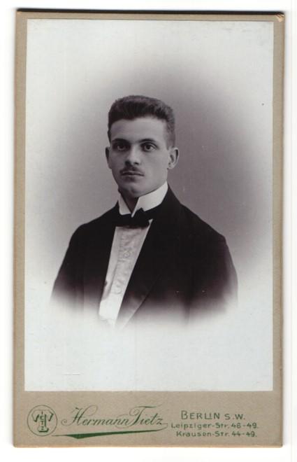 Fotografie Hermann Tietz, Berlin, Portrait junger Mann im Anzug mit Fliege