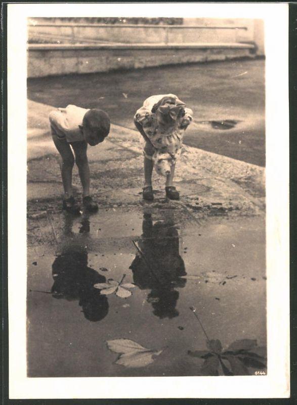 Fotografie KInder betrachten ihr Spiegelbild in einer Pfütze
