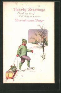 AK Hearty Greetings..., Knabe mit Schneeschuhen und Schlitten voller Geschenke