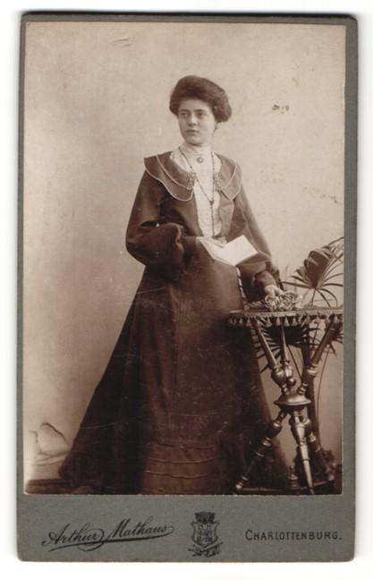 Fotografie Arthur Mathaus, Berlin-Charlottenburg, Dame mit Buch im modischen Kleid