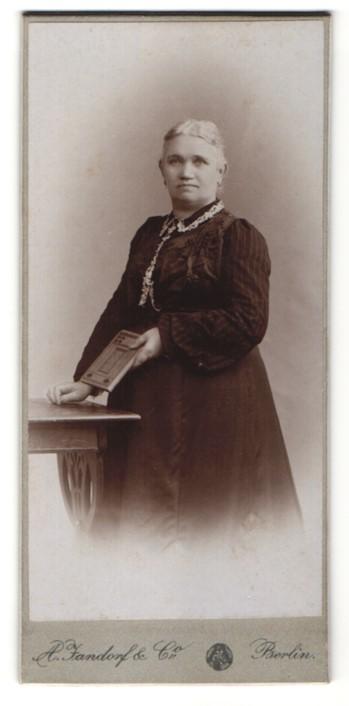 Fotografie A. Jandorf & Co., Berlin, Edeldame mit Buch im schwarzen Kleid