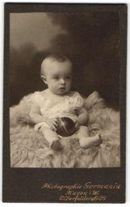 Fotografie Atelier Germania, Hagen i. W., Baby mit Ball auf Felldecke sitzend