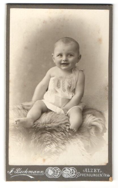 Fotografie J. Beckmann, Alzey, Baby im weissen Kleidchen auf Fell sitzend