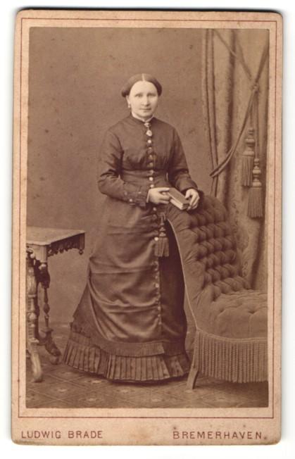 Fotografie Ludwig Brade, Bremerhaven, Edeldame mit Buch trägt elegantes Kleid