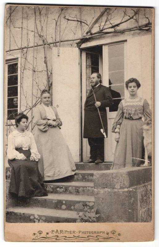 Fotografie F. A. Ritter, Ort unbekannt, Mann mit Vollbart raucht Pfeife, Damen mit Hund elegant gekleidet