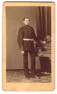 Fotografie Carl Nüchtern, Hamburg-St. Pauli, Portrait Soldat in Uniform lehnt am Kaminsims