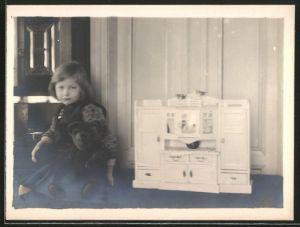 Fotografie Mädchen spielt mit Teddybär und Puppenküche