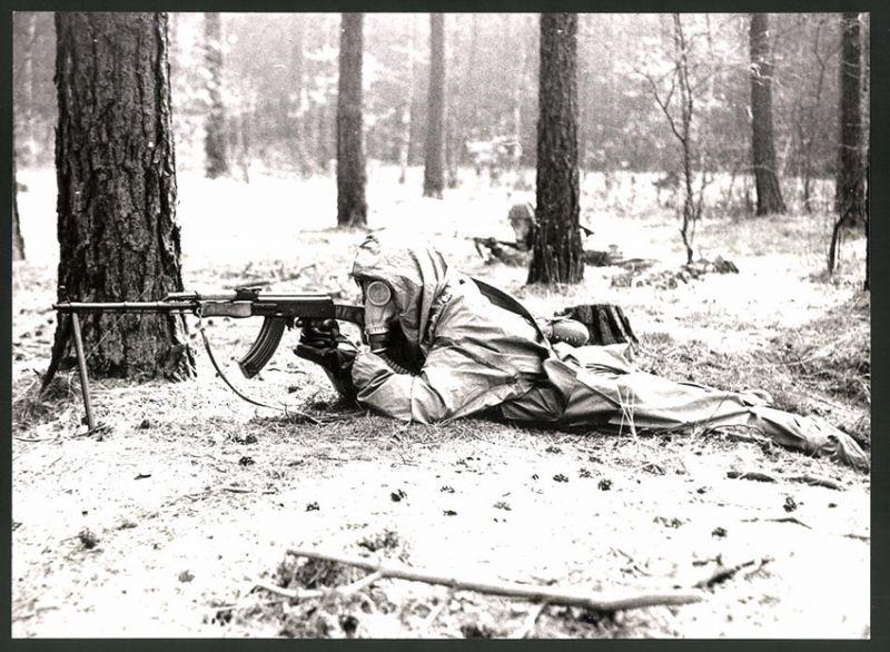 Fotografie DDR-Kampftruppe der Arbeiterklasse, Soldat im ABC-Schutzanzug mit Sturmgewehr AK-47