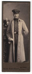 Fotografie Heinr. Schellhorn, Hamburg-Altona, Portrait Soldat in Uniformmantel