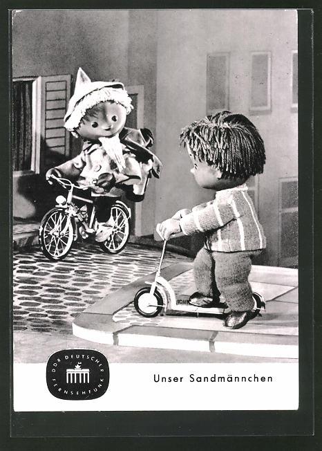 AK Sandmann trifft beim Fahrrad fahren einen kleinen Jungen auf dem Roller