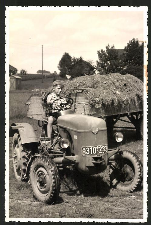Fotografie Traktor, Bauernknabe steuert Schlepper mit Anhänger voll Heu, Kfz-Kennz.: AB310-233