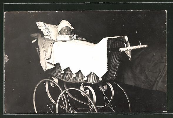 Foto-AK Baby mit Mütze liegt in einem Kinderwagen