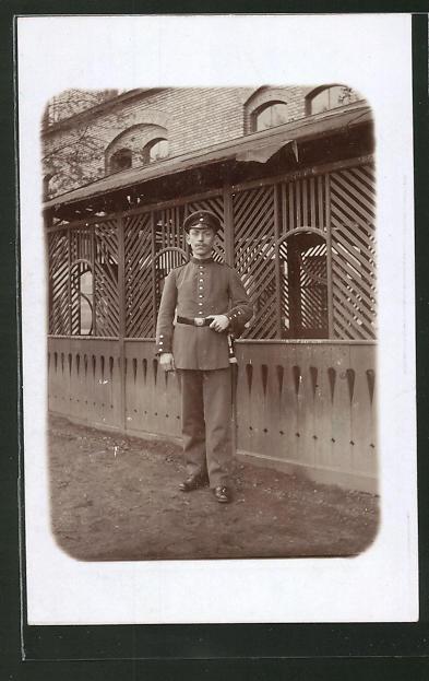 Foto-AK Soldat in Uniform steht vor einem Haus