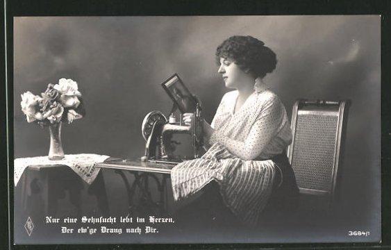 AK Näherin sitzt an der Nähmaschine und hält das Bild ihres Liebsten in den Händen