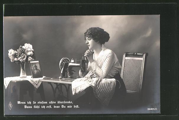 AK Frau sitzt an der Nähmaschine und betrachtet das Bild ihres Geliebten