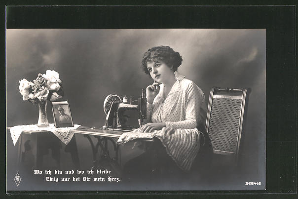 AK Frau sitzt an der Nähmaschine und denkt an ihren Liebsten