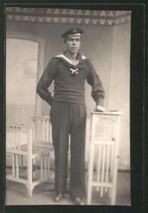 Foto-AK Matrose in Uniform steht an einem Tisch, U-Boot-Fahrer