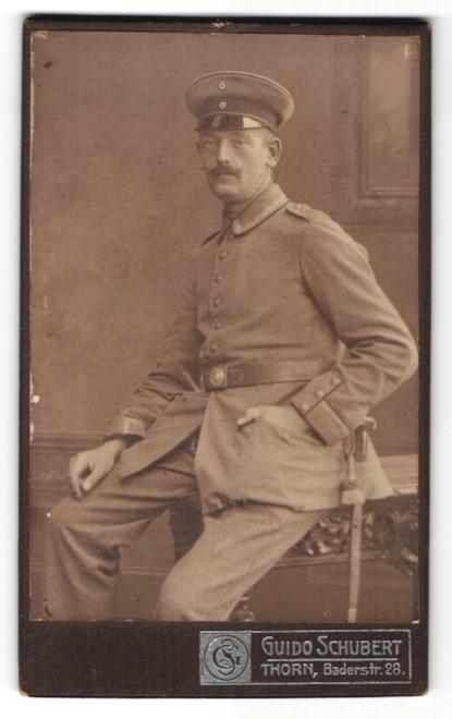 Fotografie Guido Schubert, Thorn, Portrait Soldat in Uniform sitzt auf einem Tisch