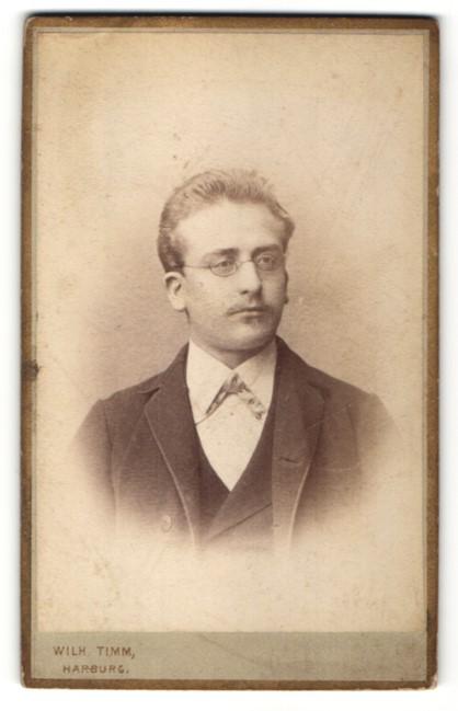 Fotografie Wilh. Timm, Harburg, Portrait eleganter Herr mit Brille