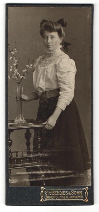 Fotografie C. F. Beddies & Sohn, Braunschweig, Portrait junge Frau mit Blumenvase