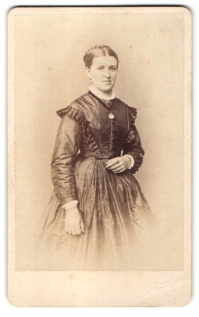 Fotografie Schroeter, Meissen, Dame mit Brosche trägt elegantes schwarzes Kleid