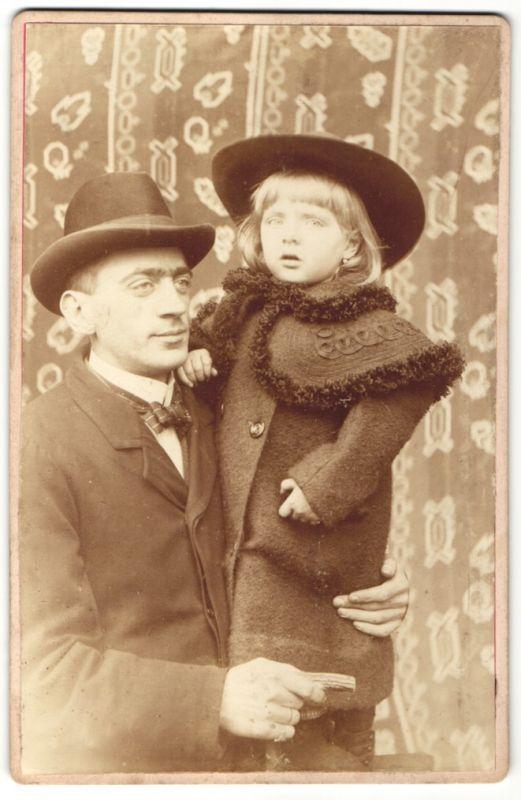 Fotografie Edelmann im Anzug hält Tochter mit modischem Mantel im Arm