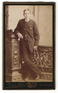 Fotografie Gebrüder Müller, Giessen, Portrait halbwüchsiger Knabe in Anzug mit Gehstock