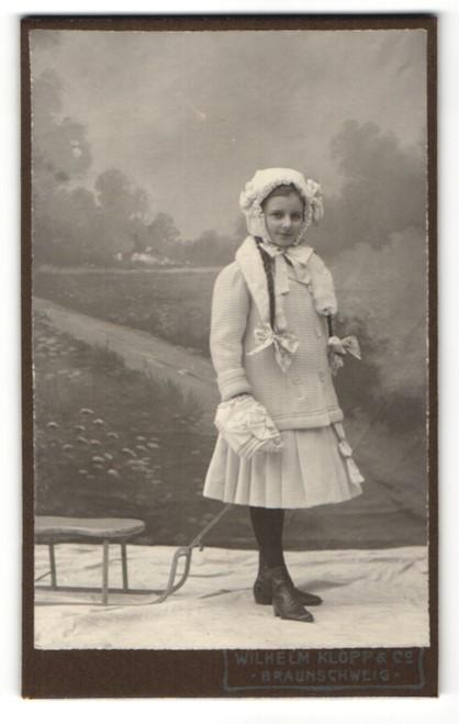 Fotografie Wilhelm Klopp & Co., Braunschweig, Mädchen mit Zöpfen in modischer Winterkleidung zieht Schlitten