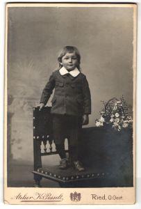 Fotografie Atelier Karl Posselt, Ried i. Innkreis, Knabe im Anzug steht auf einem Stuhl