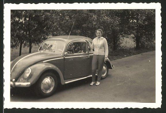 Fotografie Auto VW Käfer, junge Frau steht neben Volkswagen PKW
