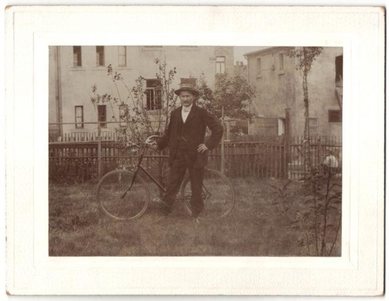 Fotografie Edelmann im Anzug mit Fahrrad im Garten