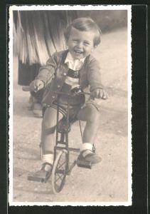 Foto-AK Lachender Knabe auf einem Dreirad