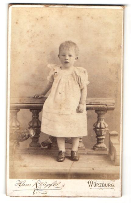Fotografie Hans Klüpfel, Würzburg, niedliches kleines Mädchen im weissen Kleid lehnt am Geländer