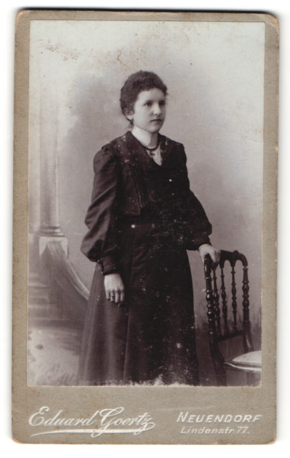 Fotografie Eduard Goertz, Neuendorf, junge Frau im hübschen Kleid steht am Stuhl
