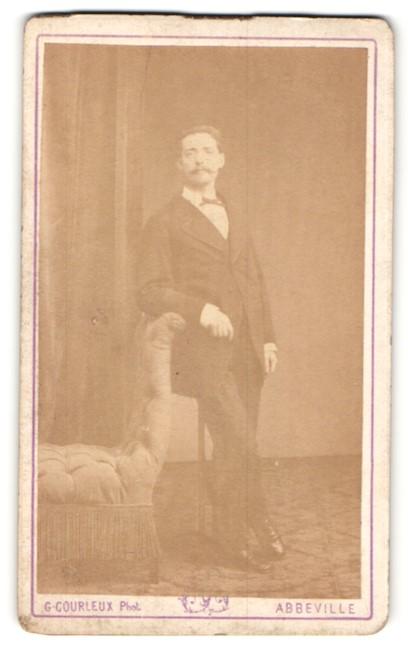 Fotografie G. Courleux, Abbeville, junger Mann mit Schnauzer im edlen Anzug an Sessel lehnend