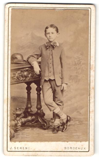 Fotografie J. Sereni, Bordeaux, frecher Bube im edlen Anzug am Tisch stehend