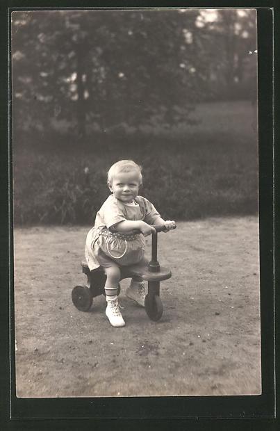Foto-AK Kleines Mädchen fährt auf einem Dreirad